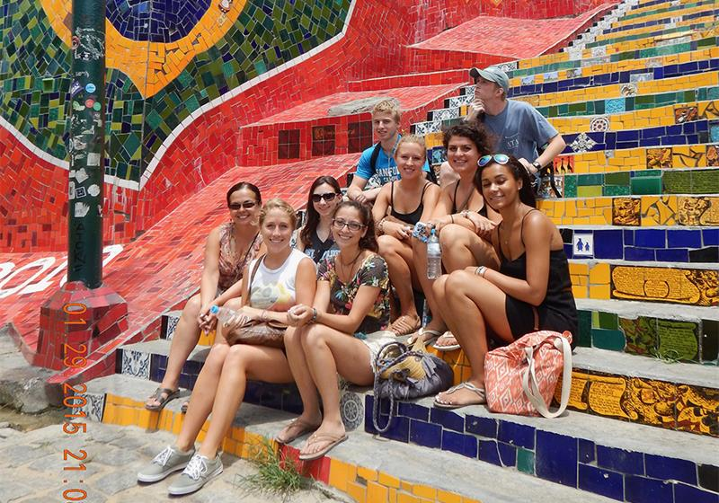 Professor Mónica Domínguez Torres and eight undergraduate students sit on colorful steps.