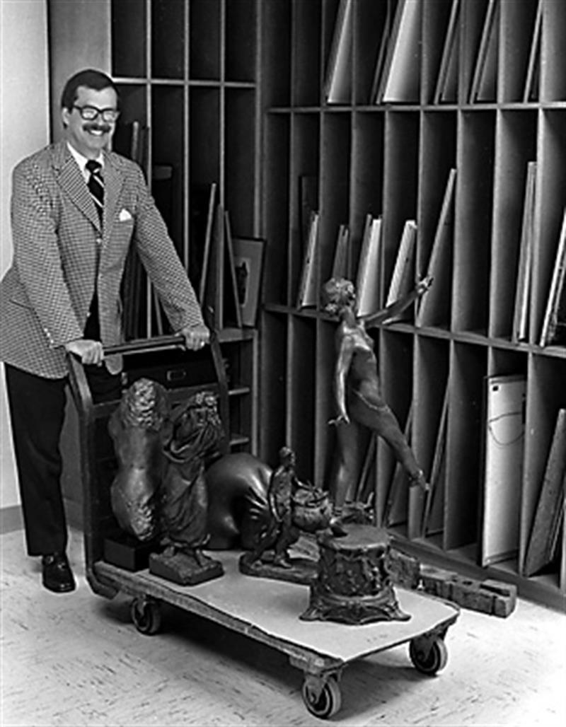 William Homer in an art storage room pushing a cart with sculptures on it